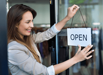 Young woman switches sign to open on door to small business